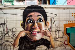 Making Faces (Matt Molloy) Tags: mattmolloy photography graffiti street art spraypaint colourful bold person kid funny face tongue tuktuk wall dirty tiles alley buildings phranakhon bangkok thailand lovelife