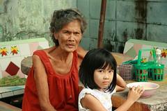 sharing great grandma's suspicion (the foreign photographer - ฝรั่งถ่) Tags: pretty girl child table bowl khlong thanon portraits bangkhen bangkok thailand canon