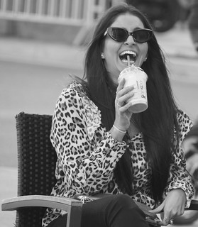 Beautiful girl drinking a milkshake at the Plaça Francesc Macià, Barcelona.