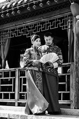 For ever (Go-tea 郭天) Tags: qingdao huangdao cangmashan shandong ancient town old traditional tradition history historical historic building construction young couple man woman lady love together union fan clothes dress dressed past family futur wedding marriage candid shooting canon eos 100d 50mm prime street urban city outside outdoor people bw bnw black white blackwhite blackandwhite monochrome naturallight natural light asia asian china chinese portrait beautiful beauty sun sunny wind windy jewelry
