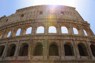 A ray of lens flare shine through the arches of the Colosseum