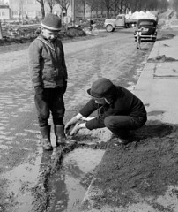 Construction (theirhistory) Tags: children kids boys pavement road street water puddle play earthdirt jacket hat trousers wellies rubberboots cap