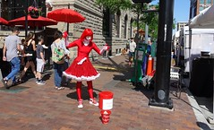 Street Performer at Saturday Market  in Boise, Idaho (lhboudreau) Tags: idaho people boise market performer streetperformer red parasol saturdaymarket boisemarket publicmarket saturday outdoor outdoors street road city sidewalk redgirl downtown building