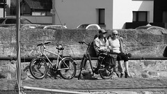 Sunny day at the harbour 04 (byronv2) Tags: sunny sunlight sunshine spring musselburgh eastlothian northsea sea river riverforth firthofforth rnbforth rnbfirthofforth forth peoplewatching candid street blackandwhite blackwhite bw monochrome coast coastal edinburgh edimbourg scotland bicycle cycle sitting seated seat bench banc man woman cycling