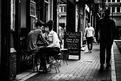 2 courses (Kieron Ellis) Tags: man woman couple sitting table chairs pavement cafe resteraunt sign embrace close street candid blackandwhite blackwhite monochrome