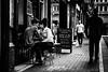 2 courses (Kieron Ellis) Tags: man woman couple sitting table chairs pavement cafe resteraunt sign embrace close street candid blackandwhite blackwhite monochrome