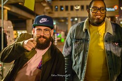 Groove is in the heart (Robica Photography) Tags: robicaphotography streetphotography straatfotografie streetart 2018 tilburg evening dim streetlights walking pavement people men hat cap glasses pointing hip groovy beard grain d3200