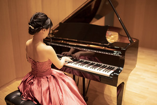Beautiful young woman playing piano in concert