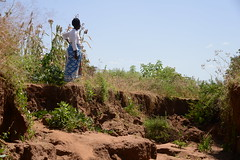 Pastor Grace Josphat viewing the gulley on her farm in Mwingi, Kenya.