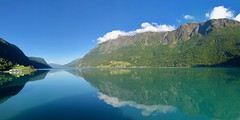 Morning on the Lustrafjord (briburt) Tags: sky cloud panorama scandinavia reflecting water morning sognefjord lustrafjord fjord skjolden norway briburt mountain landscape norwegian sun reflections forest grass blue azure zen relaxing peaceful tranquil