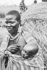 Maasai - Tanzania - Africa (TLMELO) Tags: tanzania kid boy child criança menino portrait africa masai tribe tribo serengeti poor pobre angry bravo boring kilimanjaro african africano africana retrato mount kilimanjaromount friends brothers mom son baby maasai woman hat women