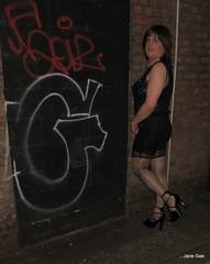 Alley Gee (janegeetgirl2) Tags: transvestite crossdresser crossdressing tgirl tv ts manchester stockings heels fishnet glamour black dress chiffon tease jane gee slip crossed legs peeking outside public platform v clip suspenders garters