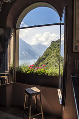 Please stay a while and have a drink (mystero233) Tags: window open view viewpoint pub bar cliff restaurant polarizedglass chair summer italy europe lagodigarda garda lake water tree grass green clouds inside indoor sun