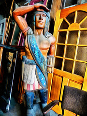 A Wooden Indian (Steve Taylor (Photography)) Tags: woodenindian cigarstoreindian looking american starsandstripes art statue sculpture carving door chair seat wooden man newzealand nz southisland canterbury christchurch indian apache antique pumphouse