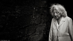 The widows tale. (Neil. Moralee) Tags: neilmoralee nikonalnwick2018 woman lady mayure old widow dark alone hair frizzy wild sorrow pain anguish lonely tired sad sadness berwick tweed black white street candid bw blackandwhite mono monochrome wall sinister wife neil moralee nikon d7200 grain grainy iso high bad tussled windswept bandw struggle bewildered upon