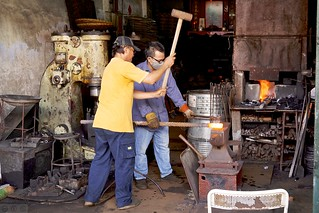 Black Smiths shaping an Iron rod.