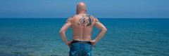 Sea view, bald headed poser. . . (CWhatPhotos) Tags: cwhatphotos cyprus protaras eastern pose shades sunglasses sun look tattoo tattooed bw portrait man male sunny day waters 2018 april digital camera pictures picture image images photo photos foto fotos that have which contain olympus seafront golden coast beach blue sky skies holiday water sea deep color colour 43 micro four thirds penf muscles muscle torso body men back rear dragon dragontattoo