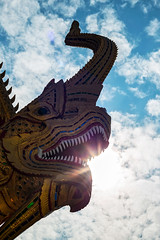 Bite the Sun (Matt Molloy) Tags: mattmolloy photography watkhuankhama buddhist temple unicornsnake naga snake serpent sculpture fancy details intricate red blue green gold colourful decoration lines scales guardian sharp teeth open mouth scary horn religion sun sky clouds light rays beams flare chiangmai thailand lovelife