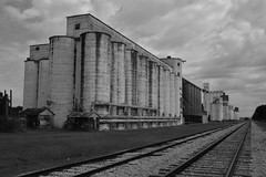 Old rice dryer and silos_DSC0731 copy (richardsscenery) Tags: rice ricesilo ricedryer katytexas praisegrass railroadtracks railway oldbuildings blackandwhite bw historyofkaty historyoftexas nikoncamera grass cloudyskies clouds gravel