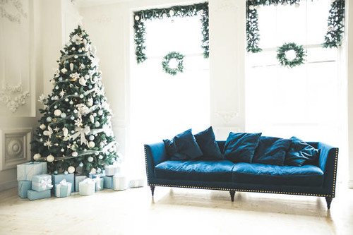 Christmas living room with a Christmas tree, sofa, gifts and a large window - Credit to https://www.lyncconf.com/