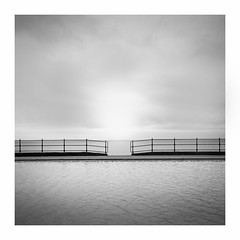 Serenity (Charles Connor) Tags: blackandwhite mono monochrome symmetry serenity calm water clouds contrasts colour ripples squareformat llandudnopaddlingpool llandudno northwales prom canon5d3 canonef24105mmlens