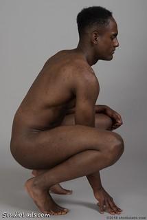Naked man squatting