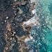 Bird eye view of ocean waves breaking of rocky shore / Vogelperspektive von den Ozeanwellen, die vom felsigen Ufer brechen