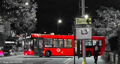 Late Night Trip To Potters Bar (M C Smith) Tags: pentax kp red bus man walking route 313 chingford pottersbar pavement kerb lines white letters numbers symbols yellow posts trees lights busstop busshelter shops cars parking lamps arrow weeds hedges awning