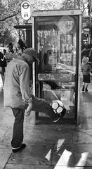 On Me Head Mate (tcees) Tags: thepavement london sw4 busstop phonebox ball people man woman child hat reflection x100 fujifilm finepix streetphotography street bw mono monochrome blackandwhite tree shop sign shadow pavement sidewalk urban taxirank football