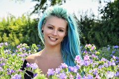 Blue and Purple beauty. (pstone646) Tags: youngwoman younglady portrait people pretty field flowers outdoors outside smile beauty longhair teeth dents sunshine