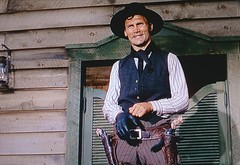 """Jack Wilson (Jack Palance), a gunfighter working for Ryker, deliberately provokes a homesteader in """"Shane"""" (1953) (lhboudreau) Tags: movie film motionpicture western wildwest cowboy classicwestern paramountpicture paramount paramountpictures 1953 color americanwest wyoming hat people screenshot gunfighter shane cattleman frontier americanfrontier saloon taunt taunting rykersman henchman rykershenchman gunslinger unscrupulous killer blackhat vest guns gun sixgun sixguns gunbelt holster holsters glove jackwilson jackpalance actor moviestar hiredgun bandana"""