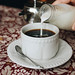 Hand pouring milk to a cup of coffee. Cafe background