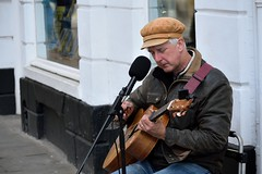 Busker #2 (Jason Khoo Photography) Tags: streetportraiture streetportrait portraiture portrait emotions thoughtful sorrow unlimitedphotos amateurphotography streetphotography culture nikond3300 people busking busker guitar man guitarist singer cambridge uk england cambridgeshire dof nikon nikkor zoomlens flickr streetpics photo photography cap british solo begging livelihood