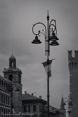 Torre della Vittoria e Torre dell'orologio - Ferrara (frillicca) Tags: 2018 april aprile bn bw bandiera belltower biancoenero bianconero blackandwhite blackwhite campanile clocktower ferrara flag italia italianflag lamp lampione monochrome monocromo nikkor nikkor18300mmf35 nikon nikond300 piazzatrentoetrieste torre torredellorologio torredellavittoria tower victorytower