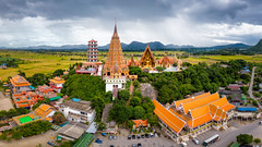 Aerial view of Wat Tham Sua Temple with rice fields in Kanchanaburi Province, Thailand. (MongkolChuewong) Tags: aerial aerialview ancient architecture art asia beautiful buddha buddhism building cave cloud clouds drone faith famous farm field golden kanchanaburi landmark landscape mountain nature pagoda panorama popular religion religious rice sacred sky spiritual statue sua sunrise sunset temple thai thailand tham top tourism travel traveler traveller view visit wat worship tambonmuangchum changwatkanchanaburi th