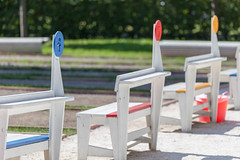 Numbered wooden chairs at a boules court