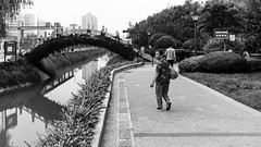 Keep an eye opened behind your back (Go-tea 郭天) Tags: qingdaoshi shandongsheng chine cn qingdao huangdao shandong bridge walk walking eyes behing back backside turn turning turned old woman lady granny grandma grandmother fun funny surprised surprise street urban city outside outdoor people candid bw bnw black white blackwhite blackandwhite monochrome naturallight natural light asia asian china chinese canon eos 100d 24mm prime movement water river canal park trees