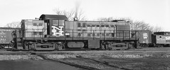 New Haven Railroad ALCO RS-1 DERS-1b class road switcher # 0664, is seen while idling in a yard area at South Braintree, Massachusetts March 6, 1961 (alcomike43) Tags: newhavenrailroad newyorknewhavenhartfordrailroadcompany southbraintreemassachusetts railroads freighttrains branchlines trains alco rs1 ders1bclass roadswitcher locomotive engine diesel dieselengine diesellocomotive dieselelectriclocomotive freightcars caboose boxcars cnr co winter tracks rails yard siding ties roadbed ballast rightofway conventionaljointedsectionrail mainline branchline anglebars spikes tieplates photo photograph negative bw blackandwhite historic old vintage classic 0664
