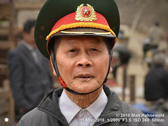 2013-07a Facing Uniforms 2018 (03) (Matt Hahnewald) Tags: matthahnewaldphotography facingtheworld real character head face eyes expression shaved headwear cap peakedcap capbadge cockade emblem coatofarms military army consent concept dedication tradition brotherhood traditional cultural officer retired bacha laocai northern asia vietnamese asian individual oneperson male elderly man photo faceperception physiognomy nikond3100 primelens 50mm 4x3 horizontal street portrait closeup headshot fullfaceview outdoor color posing authentic chewing match mouth green vietnam nikkorafs50mmf18g lookingcamera