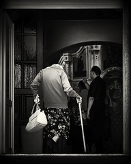 church entrance (Pomo photos) Tags: church temple religion cross blackandwhite blackwhite old man woman people bag stick shadow mood skirt street house door mono monochrome epm1 olympus olympus45mm bw
