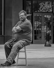 Drives a Hard Bargin (clarkcg photography) Tags: man male portrait vendor sale arms crossed footplacement sitting longday hotday stool blackandwhite blackwhite bw