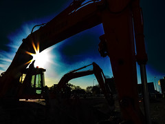 Let's Wreck and Roll (Steve Taylor (Photography)) Tags: digitalart construction demolition black blue brown green white bright metal newzealand nz southisland canterbury christchurch cbd city glare lensflare silhouette winter sunrise dawn sunny sunshine sun sky digger excavator cockpit cage hydraulics shovel