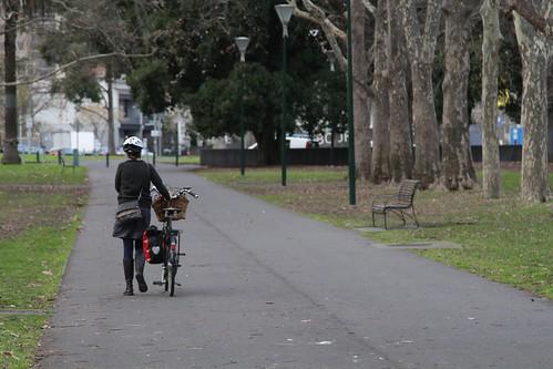 Cyclist walking their bike through the Carlton Gardens