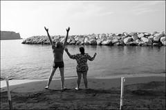 (Salute To The Sun) (Robbie McIntosh) Tags: leicam9p leica m9p rangefinder streetphotography 35mm leicam autaut candid strangers leicaelmarit28mmf28iii elmarit28mmf28iii elmarit 28mm seaside tan sand women man woman colonnaspezzata blackandwhite monochrome