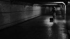 hot corridor (frax[be]) Tags: streetphotography street tunnel atmosphere gloomy dark 28mm rokkor fuji xe3 urban indoor highcontrast noiretblanc monochrome noir composition woman lowkey blackandwhite bnw bw