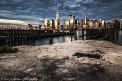 Old Docks leading to the city (ericjmalave) Tags: libertystatepark sunset twilight canonsl1 canon100d apc canon nix freedomtower newyork nyc skyline cityscape architecture lights clouds mood sigma 1020mm