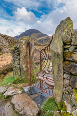 Gate To Tryfan Snowdonia (Adrian Evans Photography) Tags: snowdonia idwal tryfanmountain decorative post wales fern uk northwales trail sky gate wall footpath fence stone path cwmidwal landscape snowdonianationalpark ogwen mountains outdoor drystone llynidwal rocks irongate steps adrianevans landmark idwalgate ogwenvalley clouds tryfan track nikon 20mm