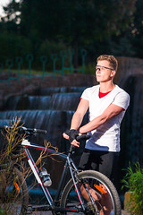 Healthy Lifestyle and Sport Concepts.Caucasian Male Athlete with Mountain Bike Posing Against Waterfall Outdoors. (DmitryMorgan) Tags: 1 20s sportsandfitness active adult athlete attractive beautiful bicycle bicyclist bike boy caucasian cheerful countryside cycle cyclinggloves cyclist exercise explorer glasses goodfit guy handsome holding lifestyle male man mountainbike nature one outdoors outside people protective ride riding safety sport sportive summer sunset travellers trip twenties