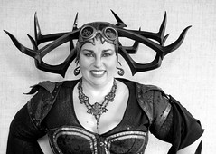 Steampunk Woman -  Hela, Thor's evil sister in Ragnarok (J Wells S) Tags: steampunkwoman smile prettyyoungwoman horns goggles blackandwhite bw monochrome portrait candidportrait internationalsteampunksymposium ramadaplaza sharonville cincinnati ohio dressup cosplay costume explore inexplore dents hela thor ragnarok gears
