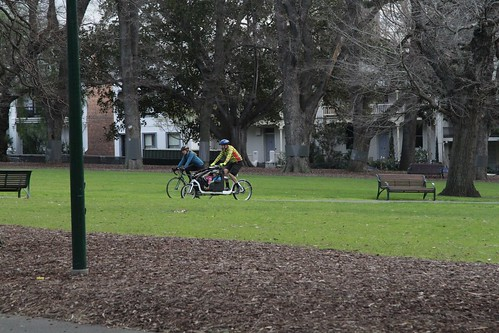 Cyclists riding their bikes through the Carlton Gardens